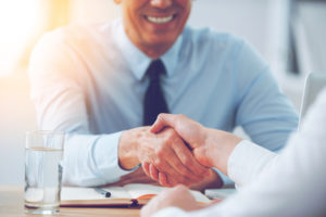 Two executives shaking hands. building a good relationship with client is crucial for Sales professionals