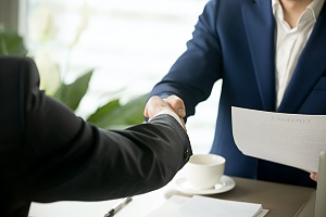 two people shaking hands after closing a sale after receiving sales negotiation consulting services