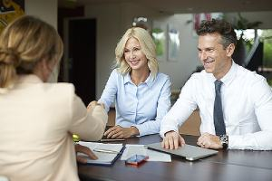 A sales professional from a Sales Management Consulting company shaking hands with one of her clients