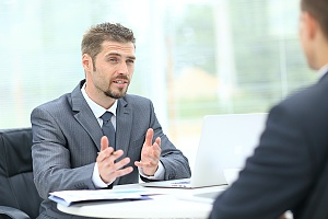 a man working for a Sales Consulting Firm handing a sales consulting firm talking with client