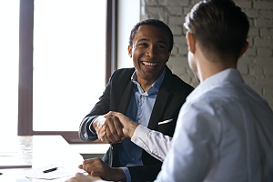 a man with experience in sales shaking hands with client