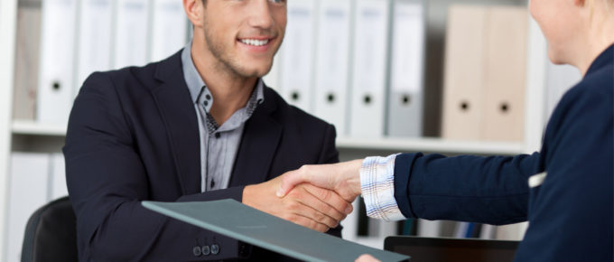 sales consultant shakes hand of the leader of sales team before they negotiate the sales compensation package