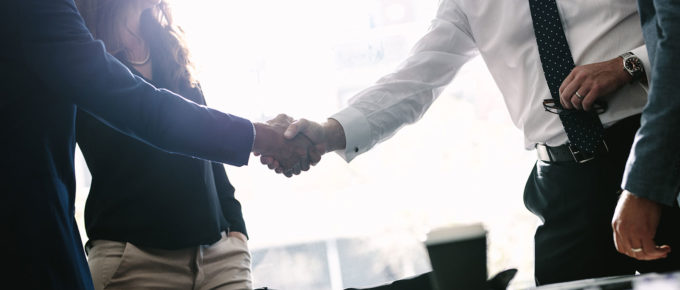 two people shaking hands after agreeing to sales management training