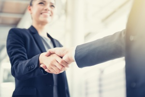 woman shaking hands after having sales management training