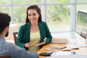 woman sitting at table going through sales management training