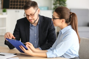 co workers looking at the benefits of a Sales Management Consulting